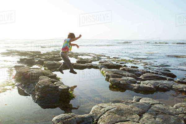 Playful boy jumping on rocks against clear sky Royalty-free stock photo