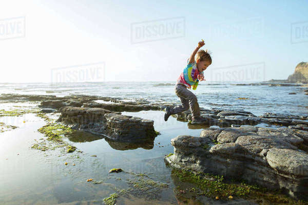 Side view of boy jumping on rocks at beach against clear sky Royalty-free stock photo