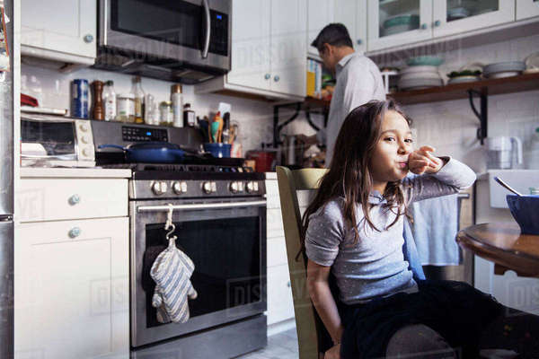 Girl sitting at table in kitchen Royalty-free stock photo