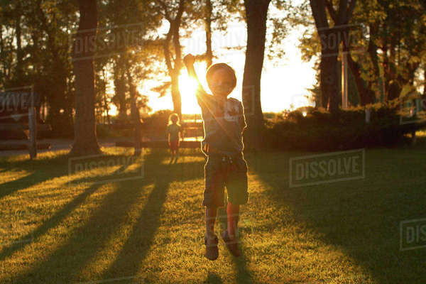 Siblings playing on grassy field in park during sunset Royalty-free stock photo