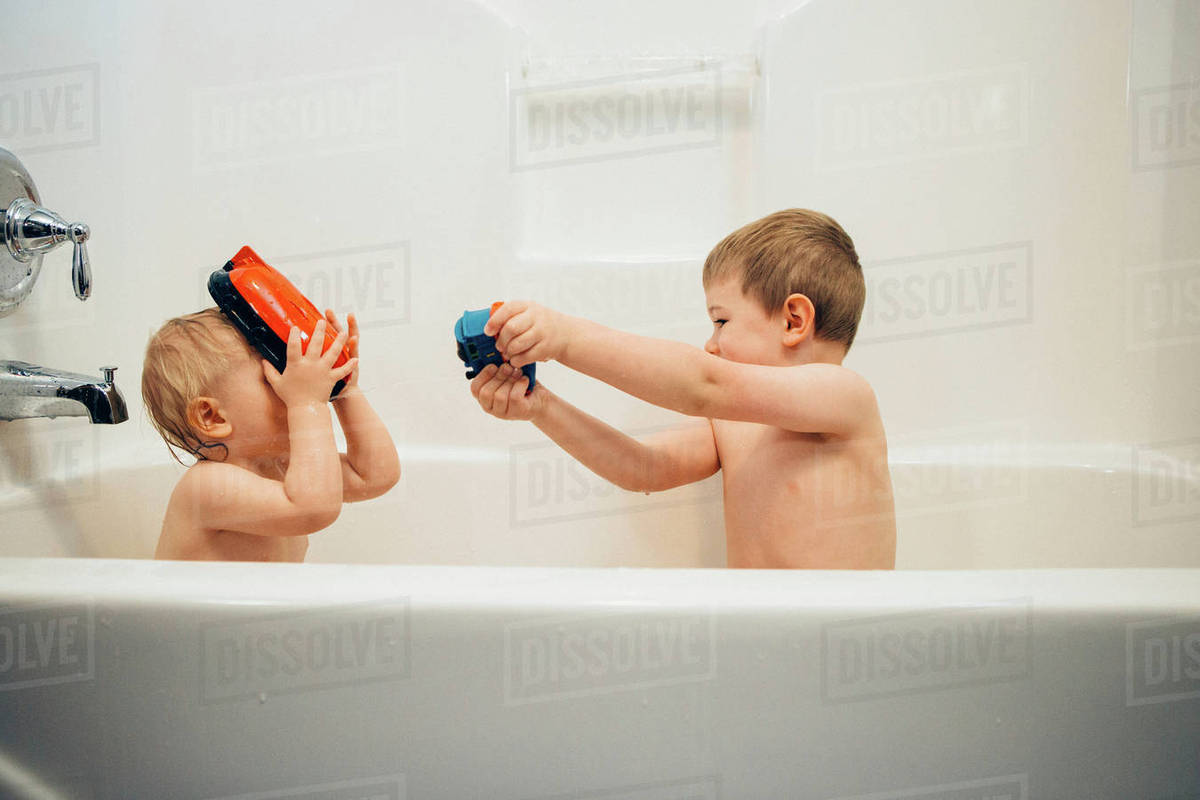 Boys playing while bathing in bathtub at home - Stock Photo - Dissolve