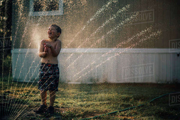 Boy enjoying water from sprinkler while standing in backyard Royalty-free stock photo