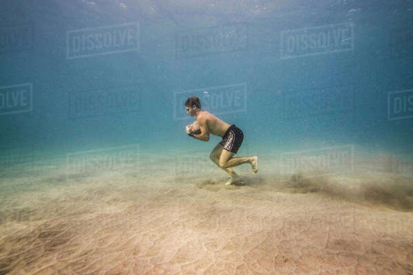 Side view of man with rock running underwater Royalty-free stock photo