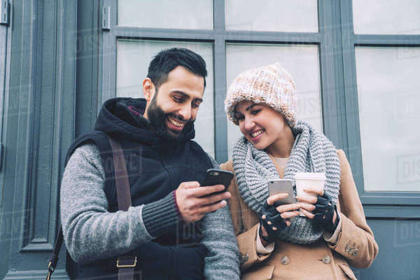 Man showing mobile phone to girlfriend while leaning by building in city Royalty-free stock photo