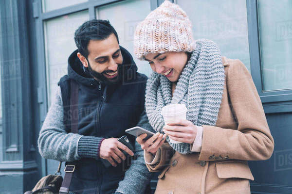 Happy couple using mobile phone while leaning by building in city Royalty-free stock photo