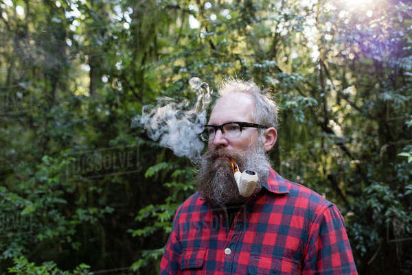 Man smoking pipe while standing against trees Royalty-free stock photo