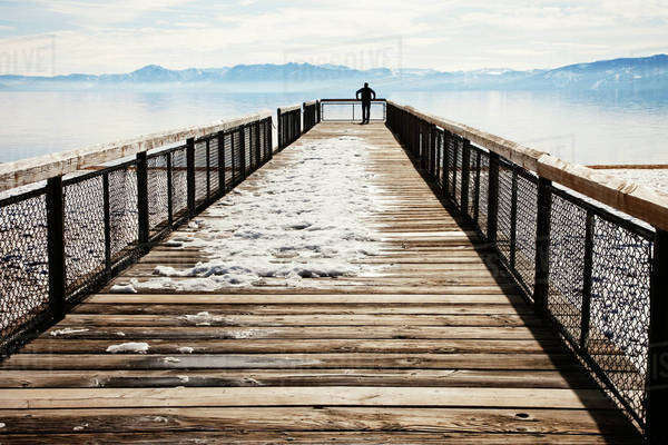 Man standing at edge of snowy pier Royalty-free stock photo