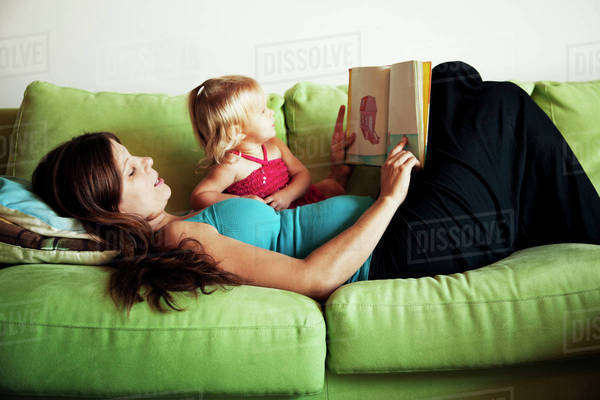 Mother reading to daughter (18-23 months) on couch Royalty-free stock photo