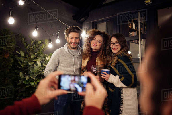 Cropped hands of man photographing friends in backyard at night Royalty-free stock photo