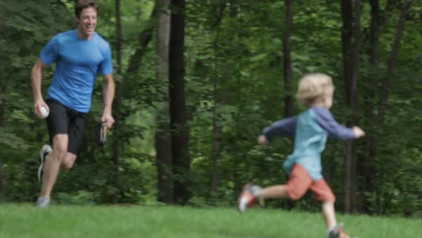 Cheerful father chasing and lifting son while playing baseball at yard Royalty-free stock video