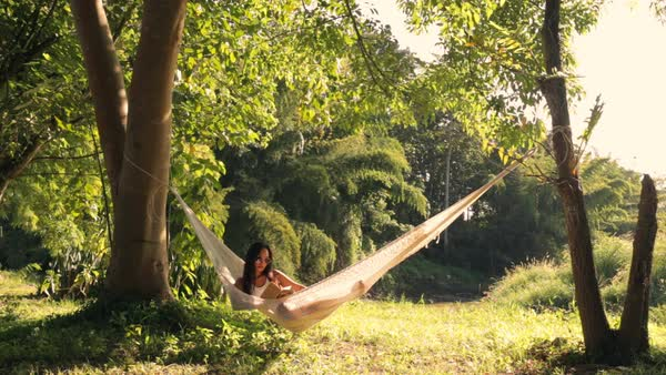 Lockdown shot of woman reading book while relaxing on hammock in forest Royalty-free stock video