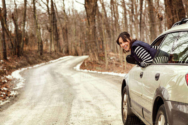 Woman leaning out car window on country road Royalty-free stock photo