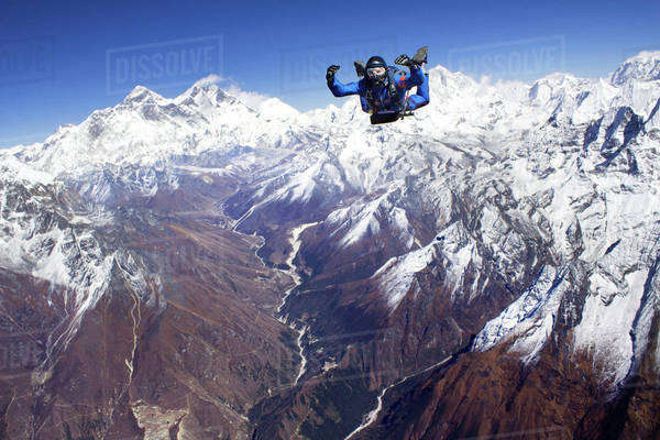 Skydiver jumping over snow-covered mountains Royalty-free stock photo