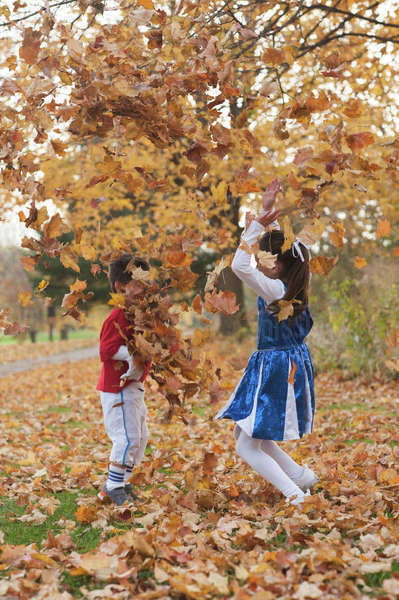 Happy siblings playing with autumn leaves in park Royalty-free stock photo