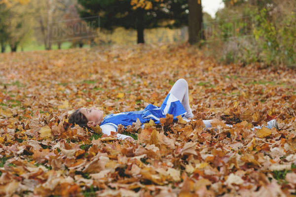 Girl relaxing on field covered with autumn leaves in park Royalty-free stock photo