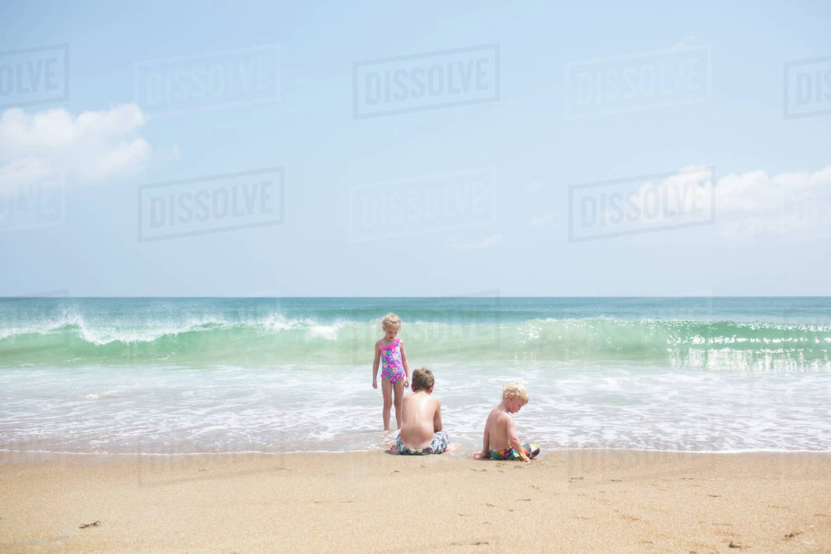 Siblings playing at beach against sky during sunny day Royalty-free stock photo