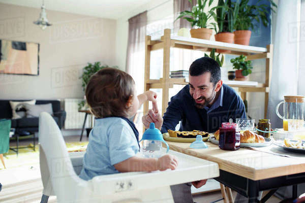 Happy father playing with son while having breakfast at home Royalty-free stock photo