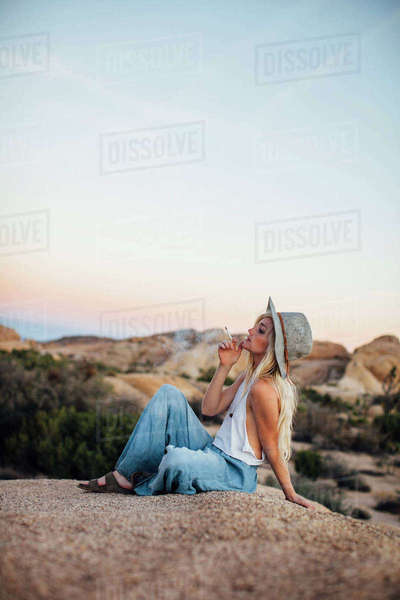 Woman smoking while sitting on rock at Joshua Tree National Park against sky Royalty-free stock photo