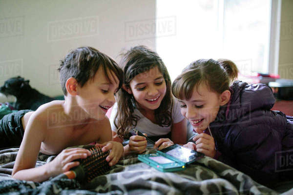 Happy siblings looking at mobile phone on bed at home Royalty-free stock photo