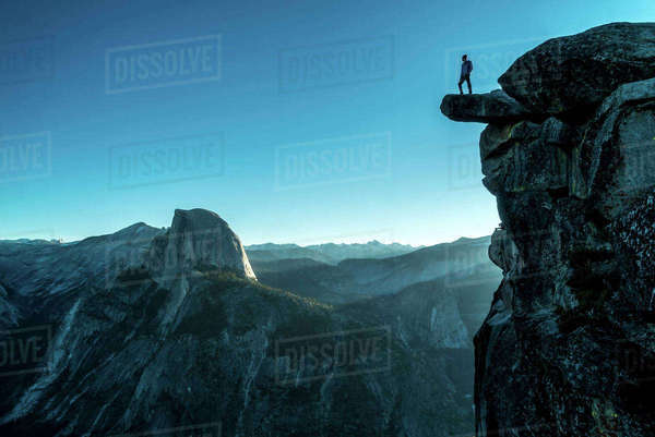Low angle view of man standing on mountain at Yosemite National Park against clear blue sky Royalty-free stock photo