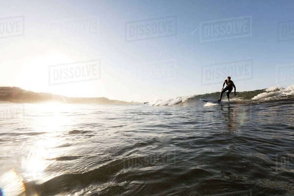 Man surfing on sea against clear sky during sunset Royalty-free stock photo