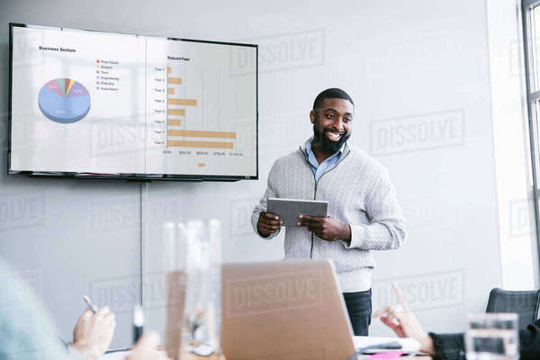 Smiling businessman holding tablet computer explaining graphs in meeting at board room Royalty-free stock photo