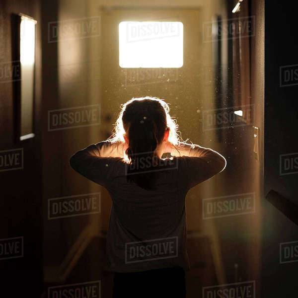 Rear view of girl standing in corridor at home Royalty-free stock photo