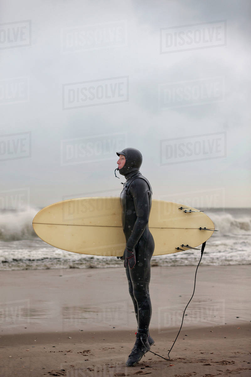 Portrait of man wearing wetsuit standing on tiptoes on sandy beach holding surfboard Royalty-free stock photo