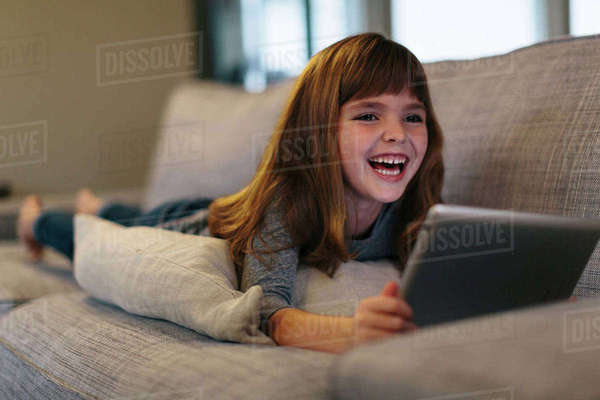 Cheerful girl using tablet computer while lying on sofa at home Royalty-free stock photo