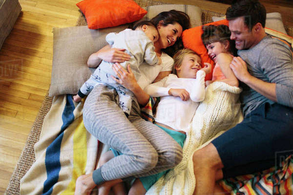 High angle view of parents with kids sleeping on carpet at home Royalty-free stock photo