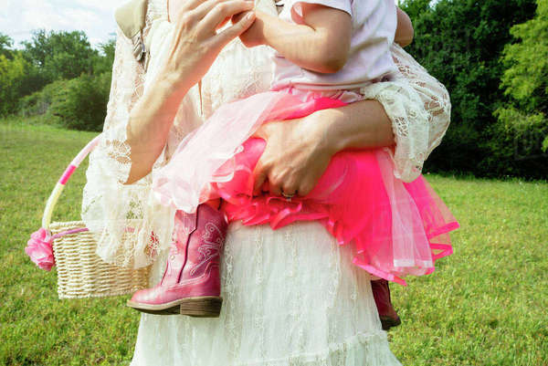 Midsection of woman carrying daughter while standing on field Royalty-free stock photo