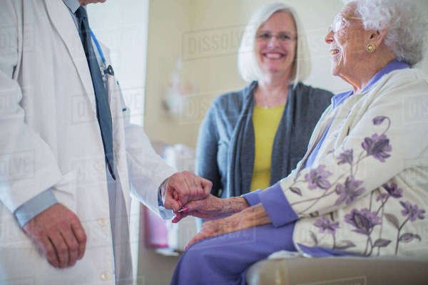 Male doctor holding hand and talking to female patient sitting by daughter in hospital ward Royalty-free stock photo