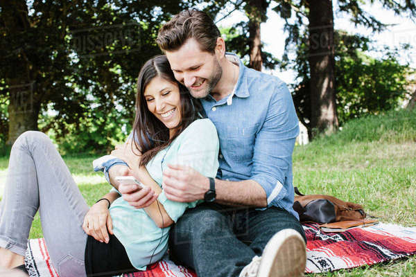 Happy couple using mobile phone while sitting in park Royalty-free stock photo