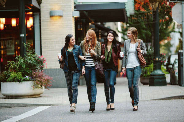 Happy female friends talking while walking on street Royalty-free stock photo