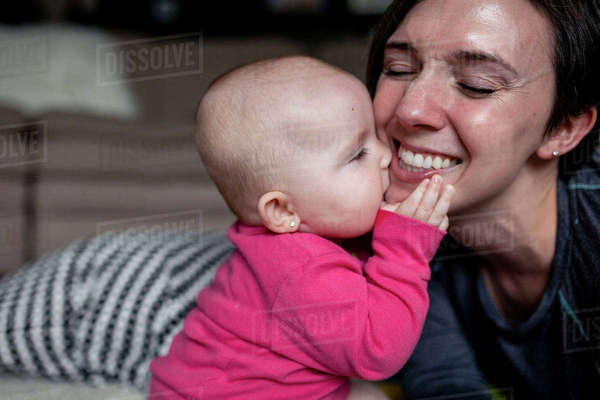 Playful daughter biting mother on bed at home Royalty-free stock photo