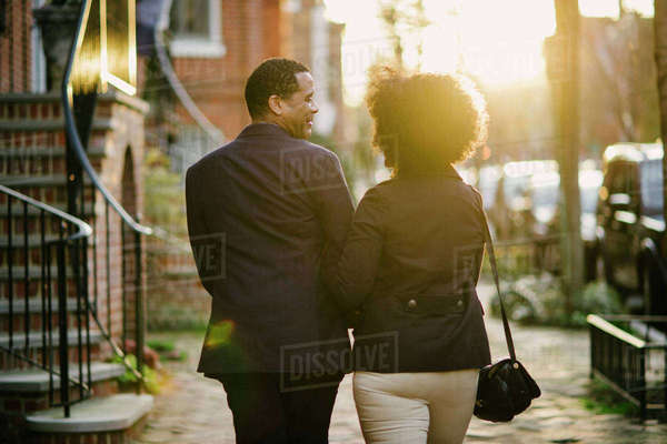 Rear view of couple walking on street during sunset Royalty-free stock photo