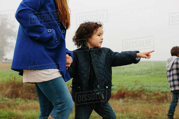 Midsection of mother walking with sons in field against sky Royalty-free stock photo
