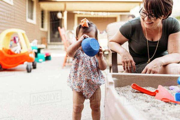 Happy mother looking at daughter playing with sand in backyard Royalty-free stock photo