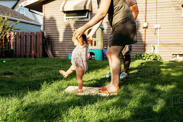 Low section of parents assisting daughter in walking at backyard Royalty-free stock photo