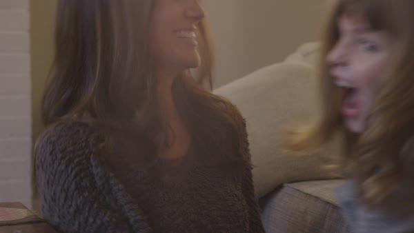Handheld shot of happy mother tickling daughter while talking to her in living room Royalty-free stock video