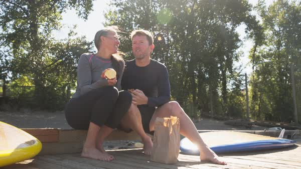 Handheld shot of couple having food while sitting on pier Royalty-free stock video