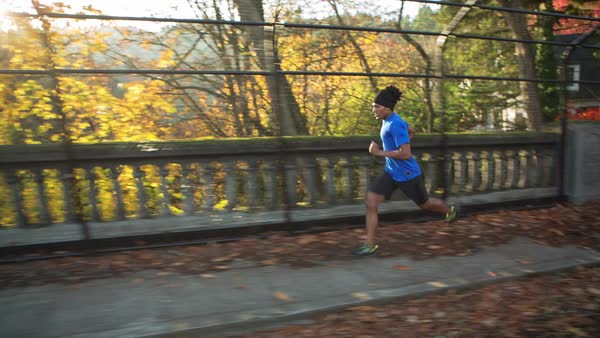 Handheld shot of male athlete running on footbridge at park during autumn Royalty-free stock video