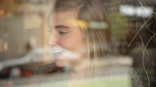 Handheld shot of happy woman talking in restaurant seen through window Royalty-free stock video