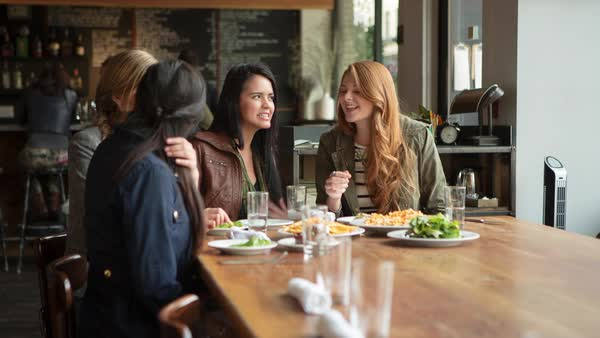 Handheld shot of cheerful friends talking while having food in restaurant Royalty-free stock video
