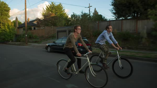 Handheld shot of friends cycling on road against houses Royalty-free stock video