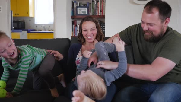 Dolly shot of happy family playing while sitting on sofa Royalty-free stock video