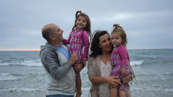Dolly shot of happy family standing on shore at beach against sky Royalty-free stock video