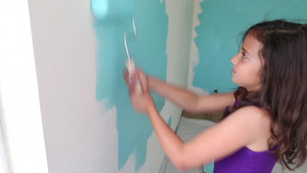 Handheld shot of girl using paint roller on wall while painting at home Royalty-free stock video