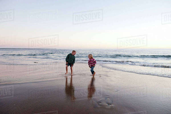 Playful siblings running on shore at beach against sky during sunset Royalty-free stock photo