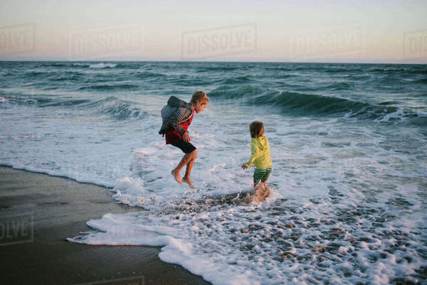 Siblings playing on shore at beach during sunset Royalty-free stock photo